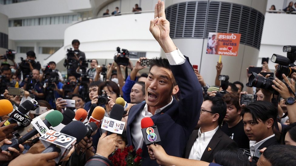 FutThanathorn Juangroongruangkit, dressed in a suit and raising his arm, is surrounded by journalists as he arrives at court