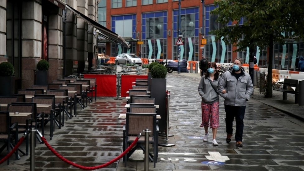 Couple walking past bar in Manchester