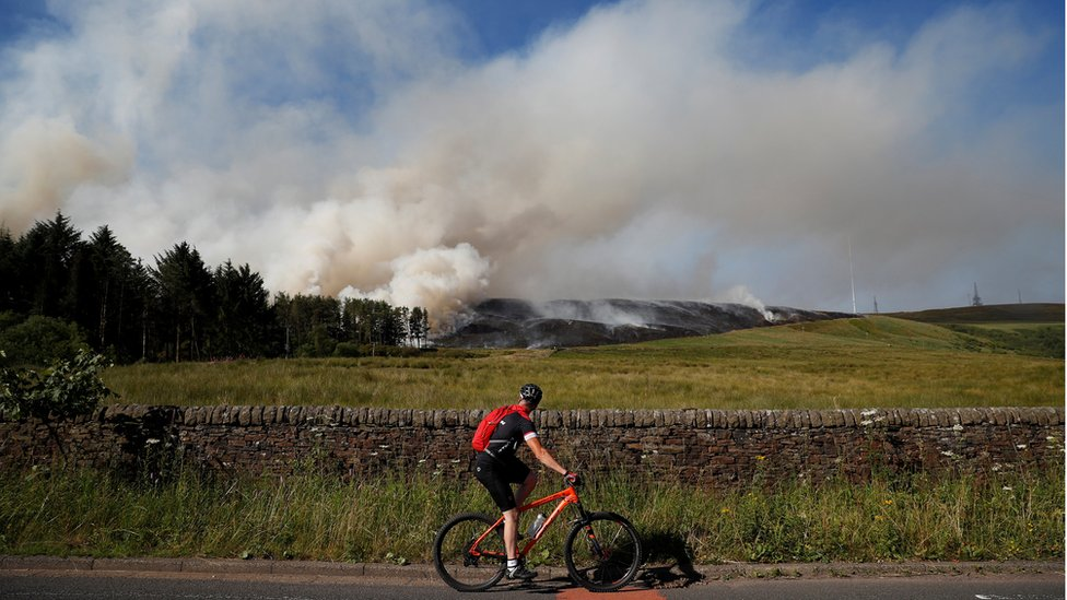 A cyclist looks at smoke rising from a moorland fire at Winter Hill, near Rivington, Britain.