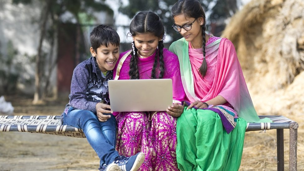 Two teenage girls and a boy, dressed in traditional Indian attire, using a laptop while sitting outdoors