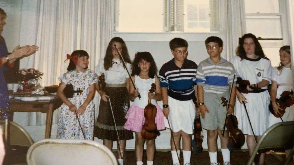 Jessica Hindman with her violin as a child - she is the third from the left
