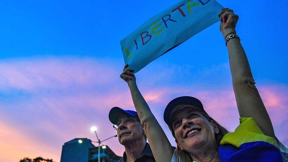Manifestante con cartel en Venezuela