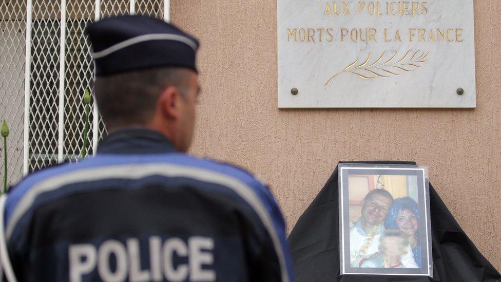 Un policía se prepara para guardar un minuto de silencio por un compañero muerto en un atentado de Estado Islámico.