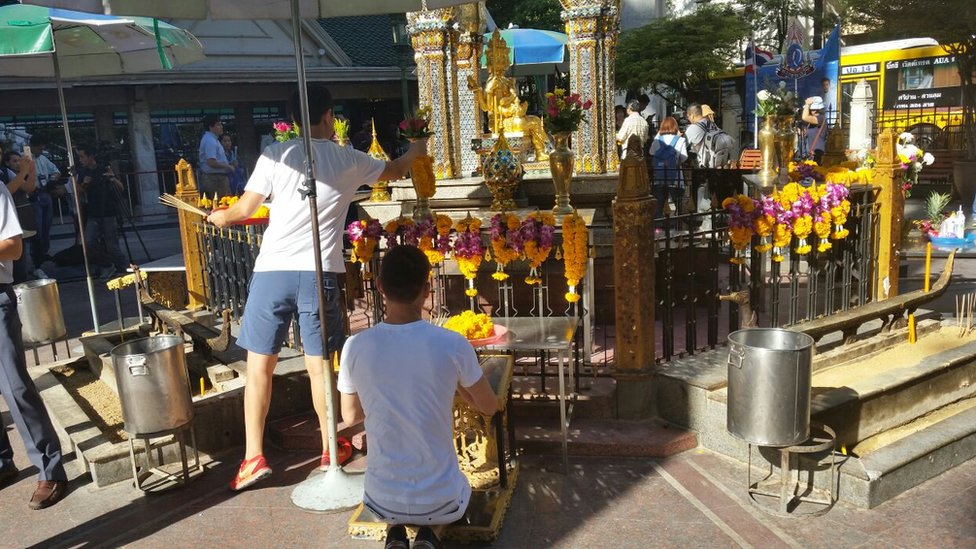 Men place flowers at the Erawan Shrine in Bangkok (19 Aug 2015)