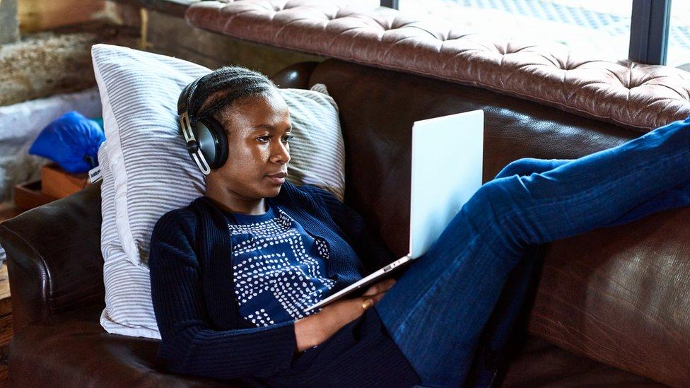 Una joven usa su laptop y lleva audífonos mientras está acostada en un sofá