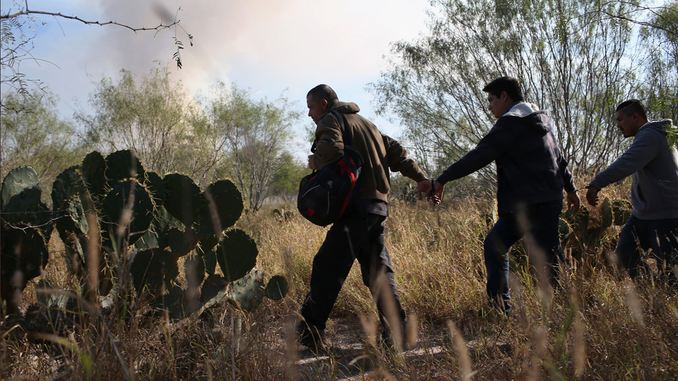 Immigrants walk handcuffed after illegally crossing the US-Mexico border and being caught by the US Border Patrol on December 7, 2015 near Rio Grande City, Texas