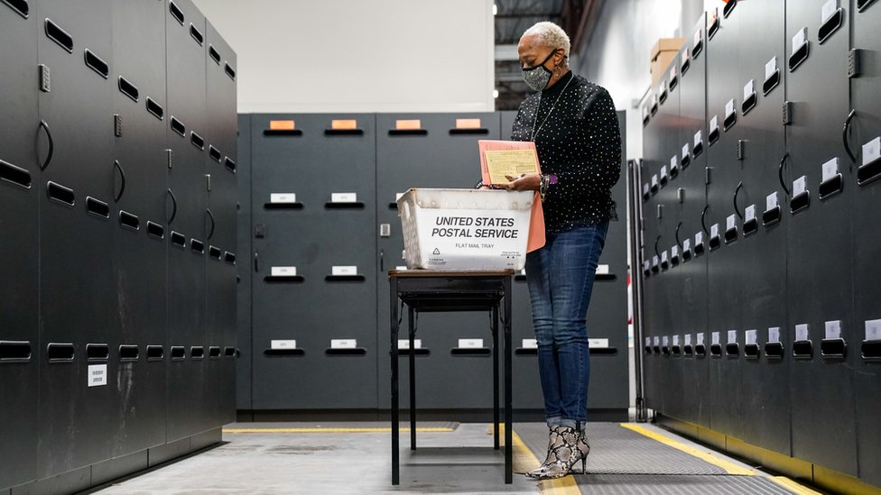 A woman surrounded by filing cabinets looking through ballots in Georgia.