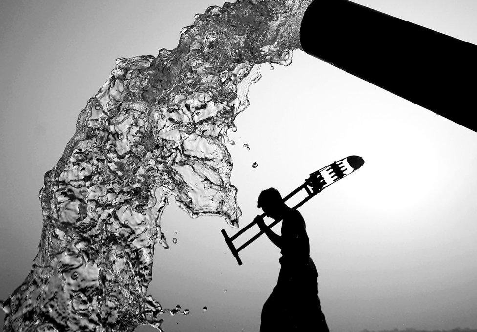 Crno-bela fotografija na kojoj se vidi kako voda izlazi iz creva dok se u pozadini primećuje silueta čoveka koji hoda