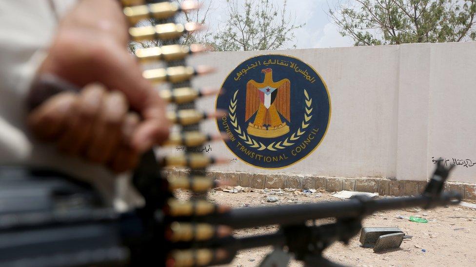 جندي تابع للحكومة اليمنية يحمل سلاحه بالقرب من شعار المجلس الانتقالي الجنوبي في مدينة عتق
