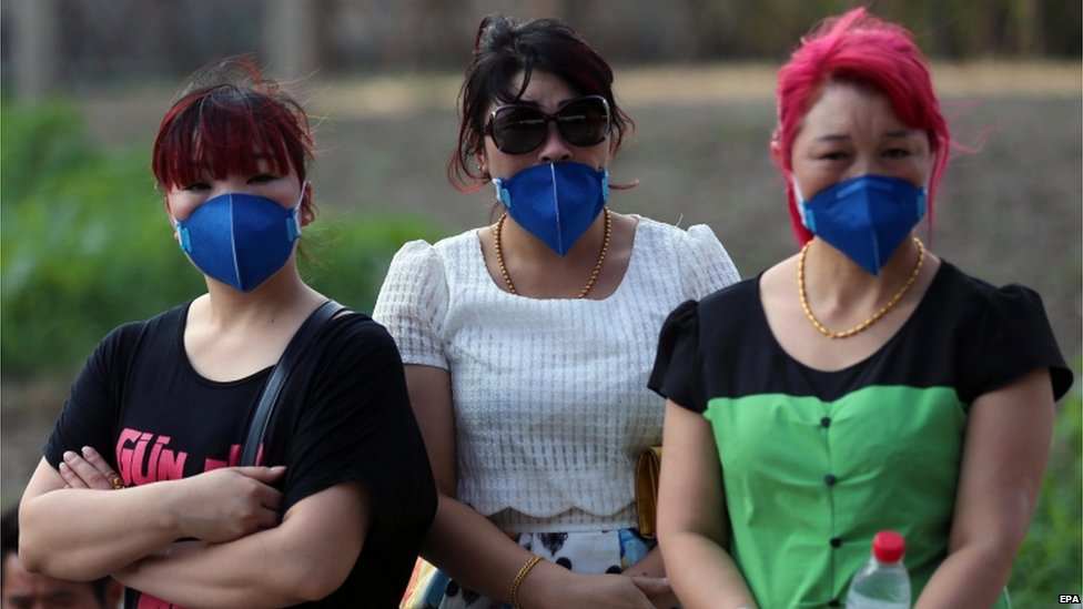 Chinese people wearing masks look on at a street after a huge explosion rocked the port city of Tianjin, China, 13 August 2015