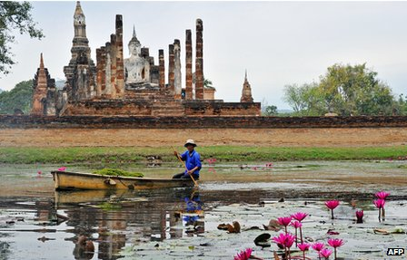 Gardener in front of ruins of Sukhothai, capital of the 13th-15th Thai-speaking kingdom of the same name