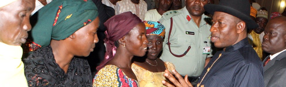 Goodluck Jonathan (R) speaks to relatives of some of the Chibok schoolgirls who escaped their Islamist captors.