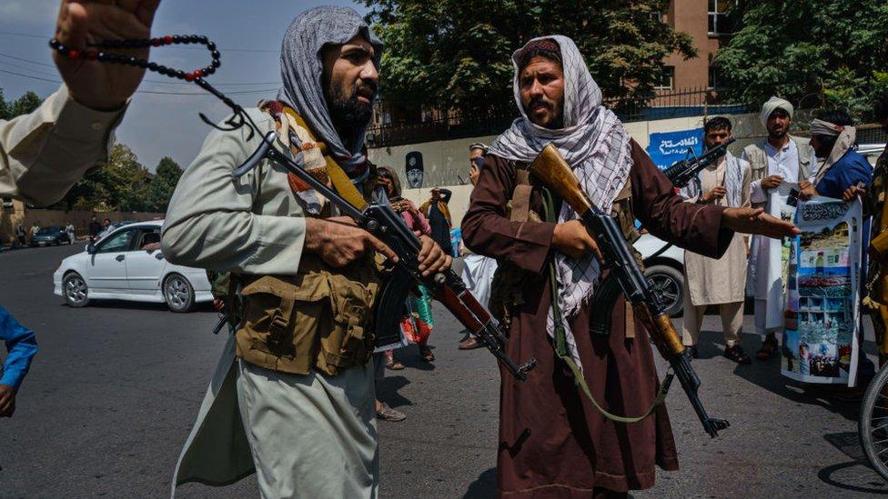 I combattenti talebani si riuniscono per controllare una folla a Kabul giovedì 19 agosto 2021.