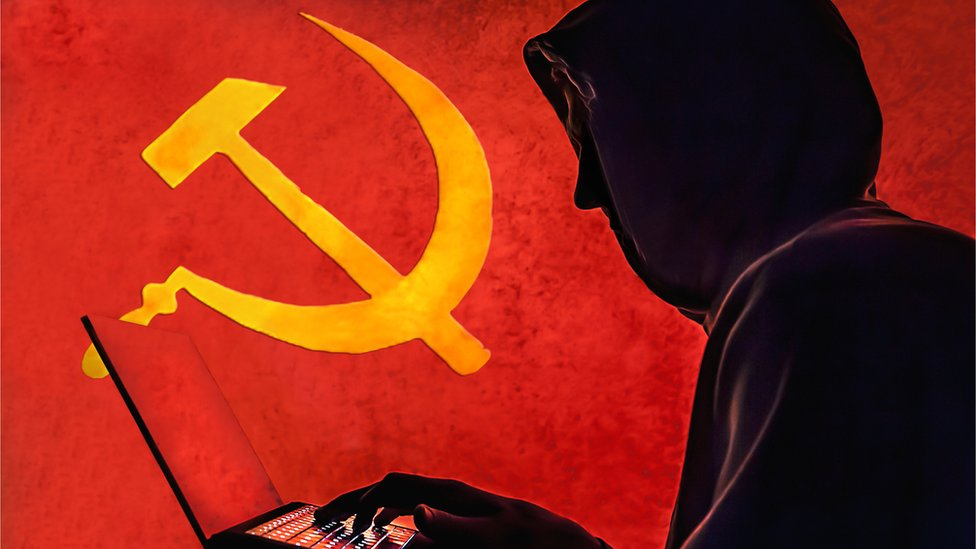 """The old Communist Russian hammer and sickle is seen in the background of a silhouetted """"hacker"""" caricature wearing a hoodie"""