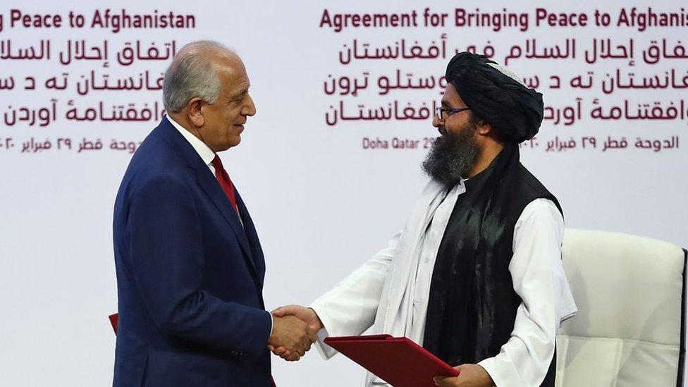 Zalmay Khalilzad y el cofundador del Talibán, Mullah Abdul Ghani Baradar, se dan la mano.