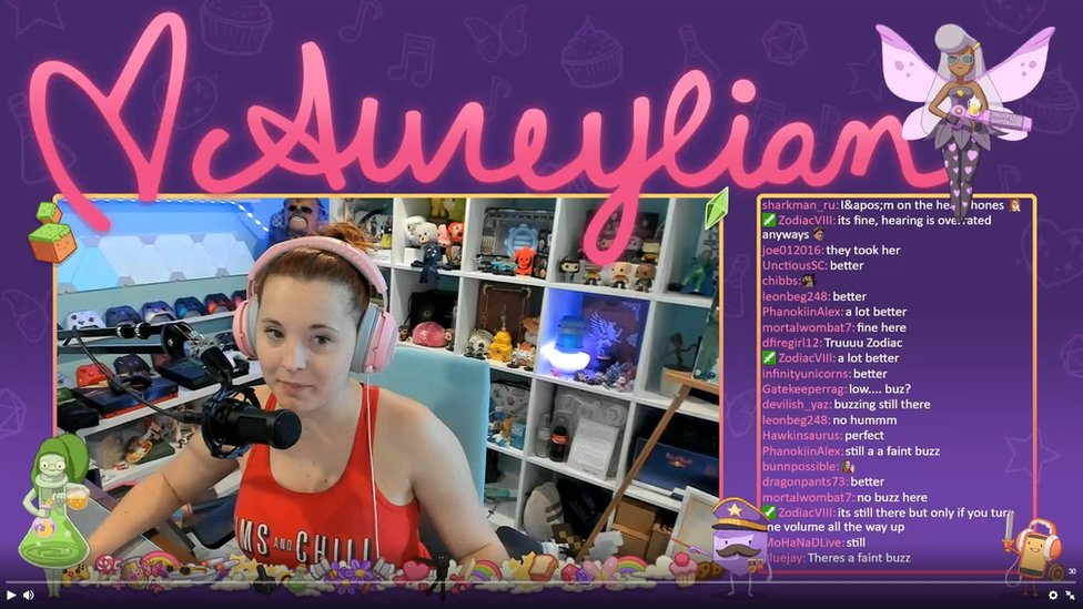 A screenshot of a Twitch stream. In the middle is the video stream featuring Aureylian, a young woman wearing a headset in front of a microphone. In the background are various gaming consoles and controllers, as well as figurines and models. The screenshot also shows a chat screen filled with various comments from her fans.