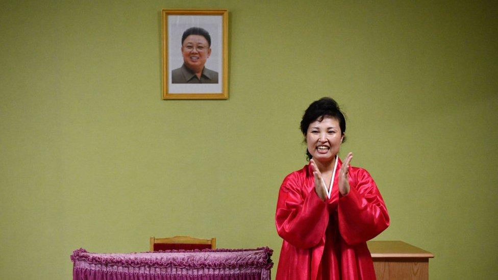 Norcoreana aplaudiendo frente al retrato de Kim Jong-il.