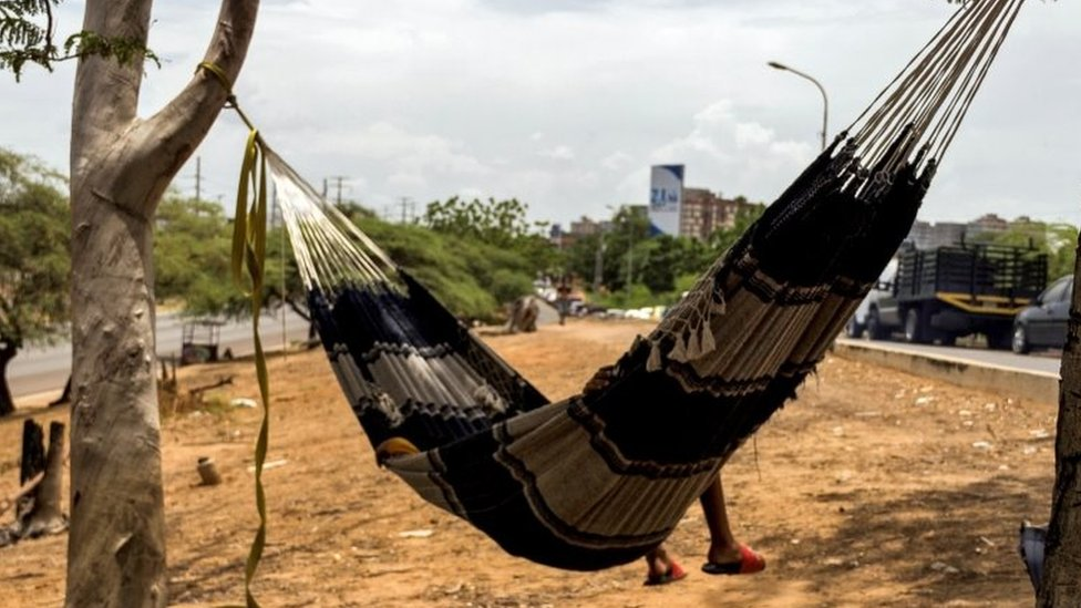 A man sleeps in a hammock as he waits next to his vehicle to load gasoline at a closed station, in Maracaibo, Venezuela, 19 September 2020 (issued 28 September 2020).