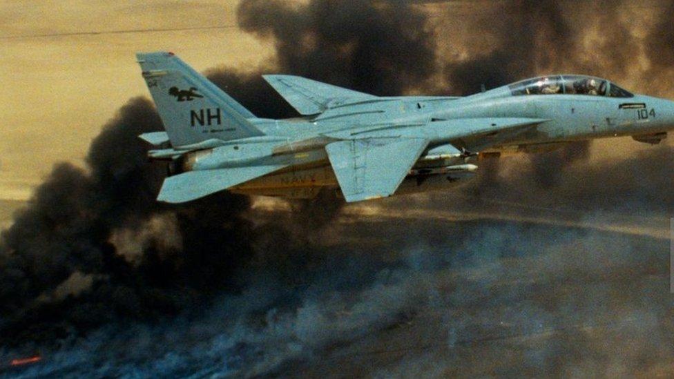طائرة تومكات تحلق فوق حرائق آبار النفط