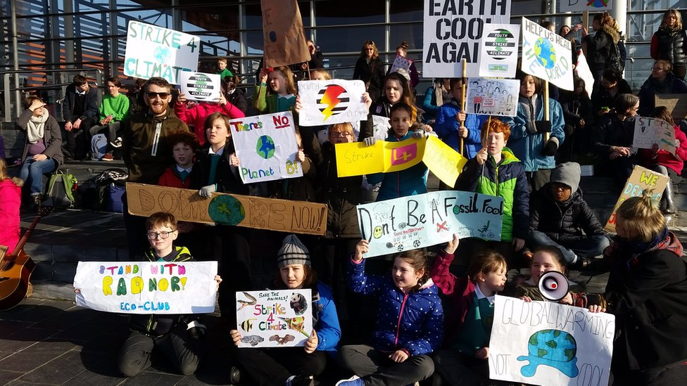 Schoolchildren holding up anti-climate change placards