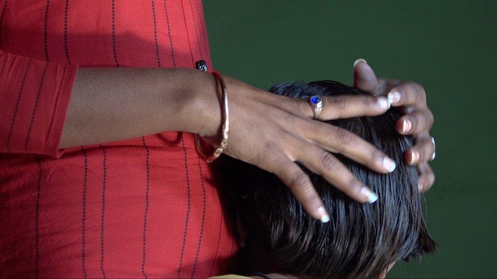 امرأة تضع يداها على رأس طفل