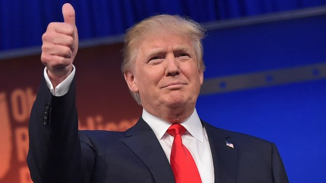 Donald Trump flashes the thumbs-up as he arrives on stage for the start of the Republican presidential debate 6 August 2015