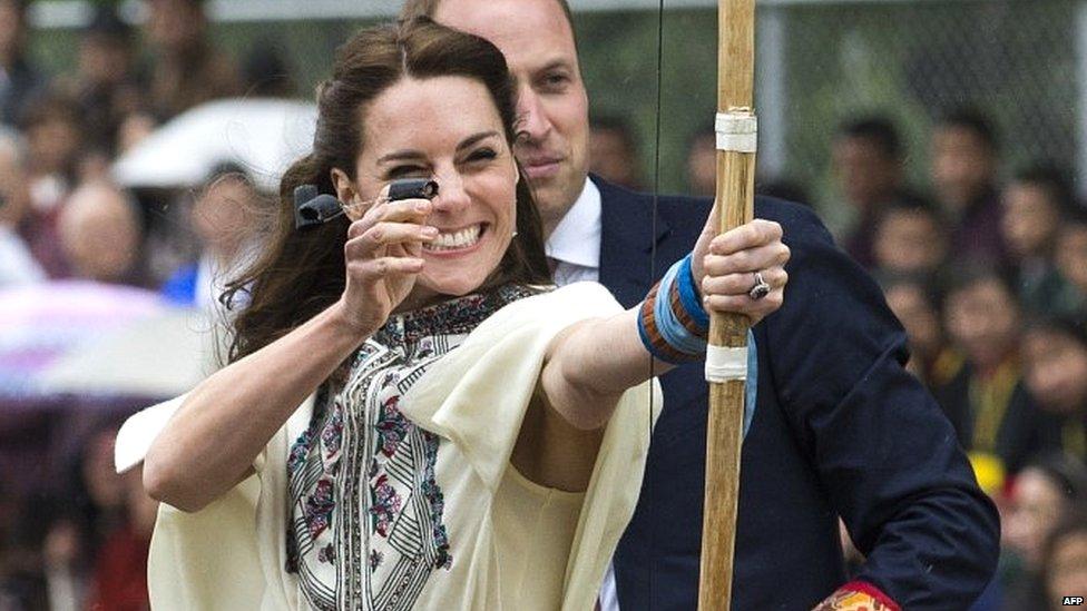 The Duchess of Cambridge fires an arrow, as the Duke of Cambridge looks on