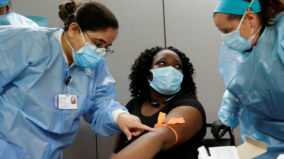 Nurses take blood from the arm of a woman