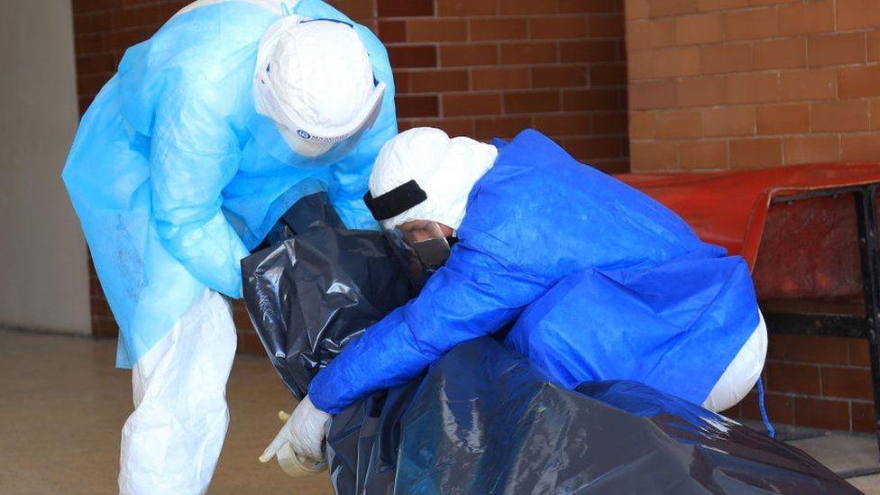 Personal de salud con un muerto en una bolsa plástica.