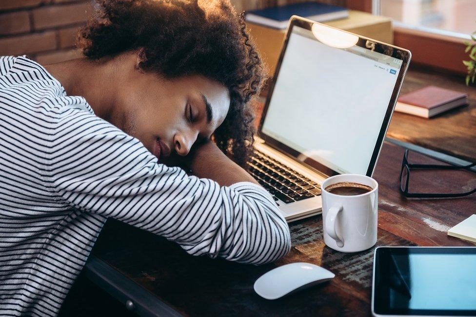 Un joven durmiendo en el teclado de su laptop.