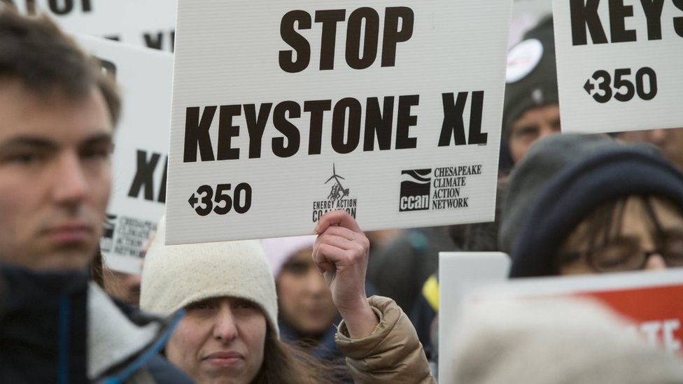 """A woman holds up a placard saying """"Stop Keystone XL"""""""