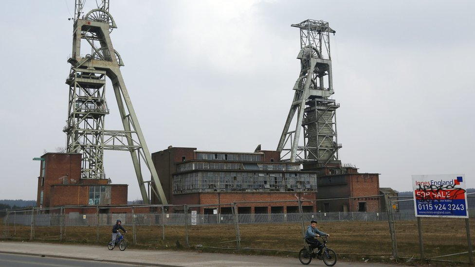 Boys cycle past the closed Clipstone Colliery in Clipstone near Mansfield