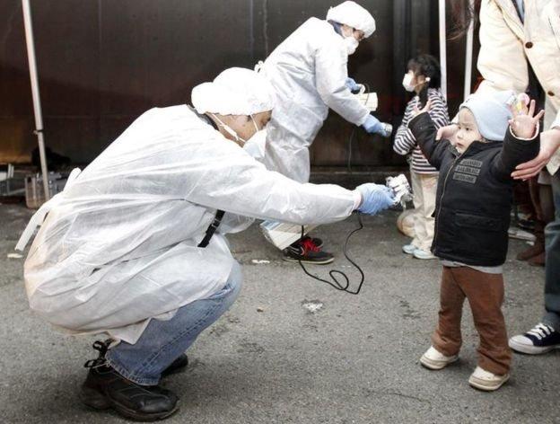 2011年福島核事故後,身穿防護衣的工作人員為兒童檢查輻射跡象。
