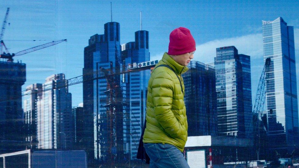 A man walks past a property developer's billboard in Beijing