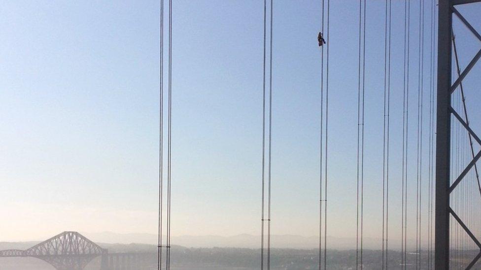 Un técnico trabajando a gran altura sobre un puente