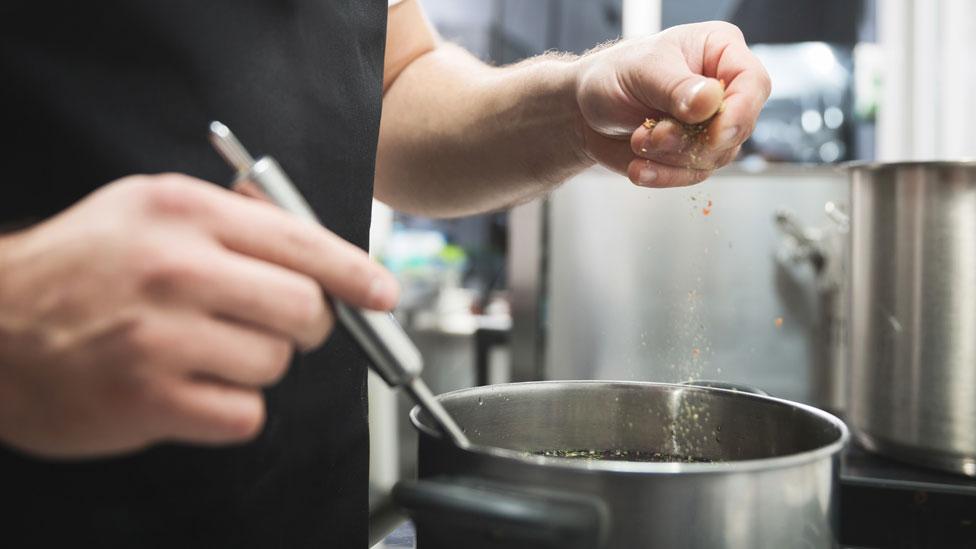 Un hombre cocinando una salsa.
