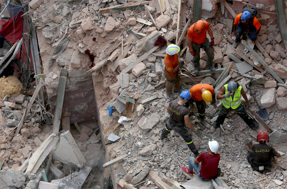 Rescuers search the rubble of a collapsed building