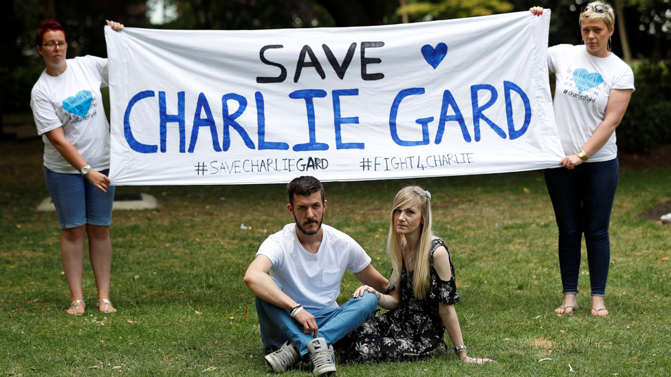 The parents of critically ill baby Charlie Gard, Connie Yates and Chris Gard, pose for photographers as supporters hold a banner, before delivering a petition to Great Ormond Street Hospital, in central London, Britain July 9, 2017