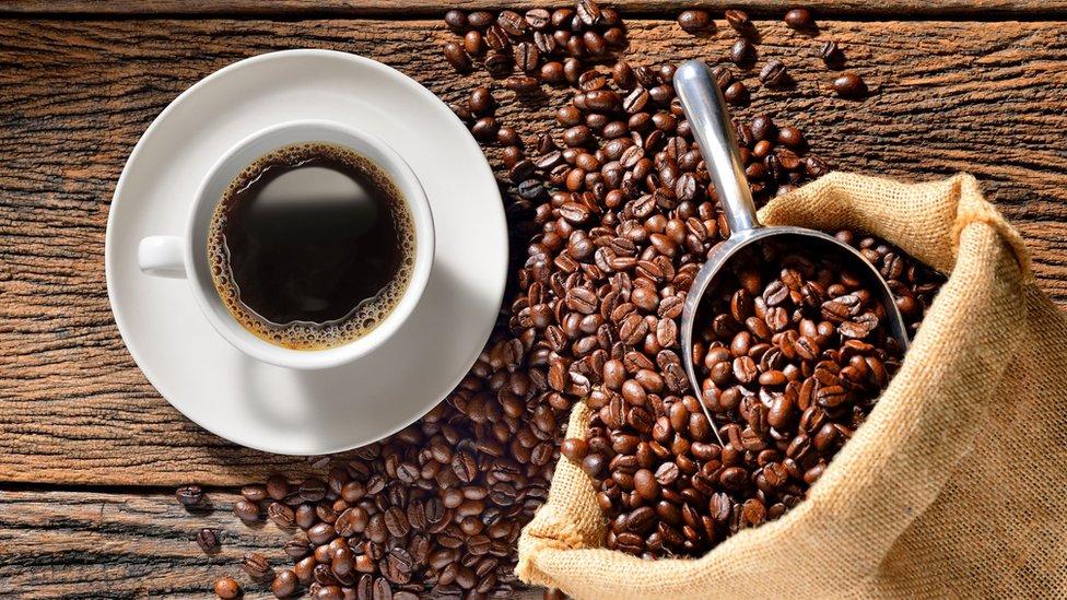 Kavrulmuş kahve çekirdeklerinin yanında kahve dolu bir fincan