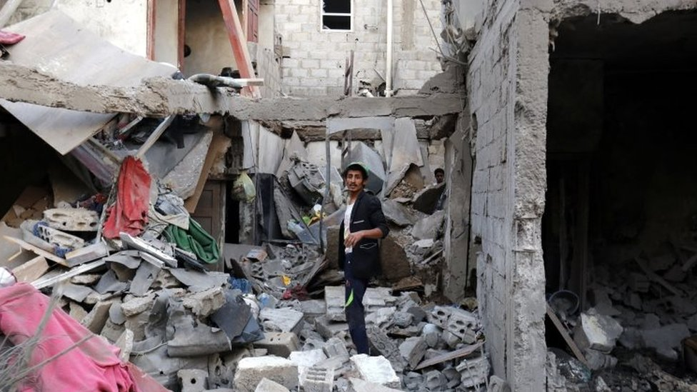 A man among rubble after an alleged Saudi-led airstrike in Yemen
