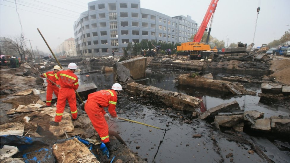 Emergency services personnel standing next to a large pool of oil and rubble