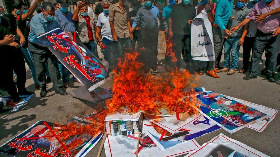 Gente quemando fotos de Trump, Netanyahu y líderes de EAU y Bahréin.
