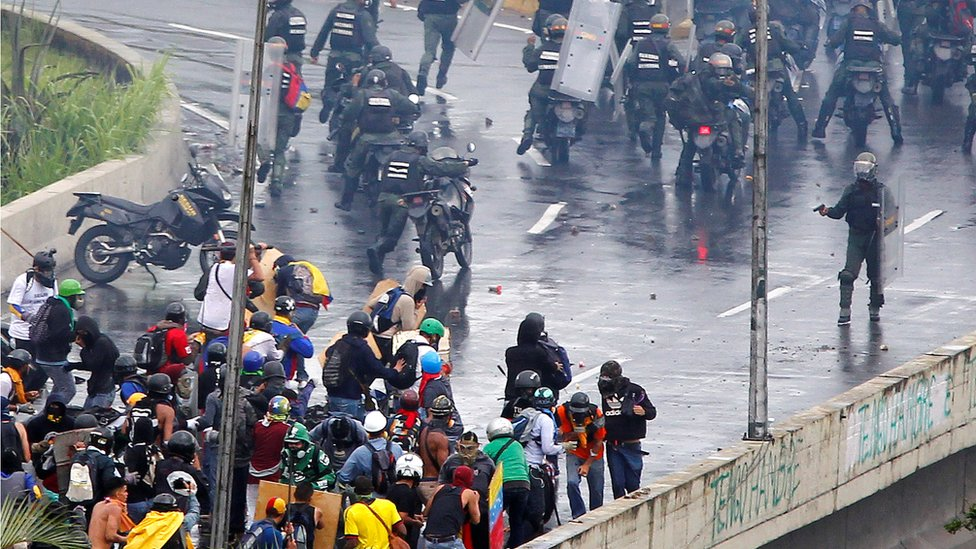 A member of the riot security forces points what appears to be a pistol towards a crowd of demonstrators during a rally against Venezuela's President Nicolas Maduro's government in Caracas, 19 June