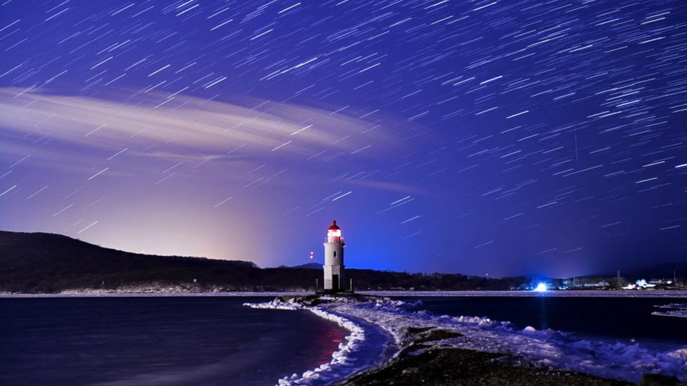 Meteore Geminidi cadono nel cielo del faro Tokarevsky a Egersheld Cape Bay, Isola Russky, Mar del Giappone nel dicembre 2017.