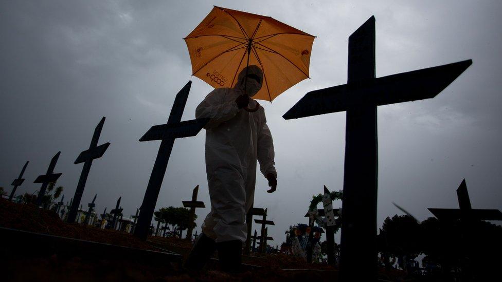 Un trabajador con traje de proteccion recorre tumbas de victimas de covid-19 en Brasil.