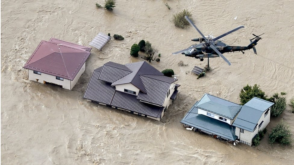 Defence force helicopter flying over residential areas flooded by the Chikuma river following Typhoon Hagibis in Nagano, central Japan, October 13, 2019