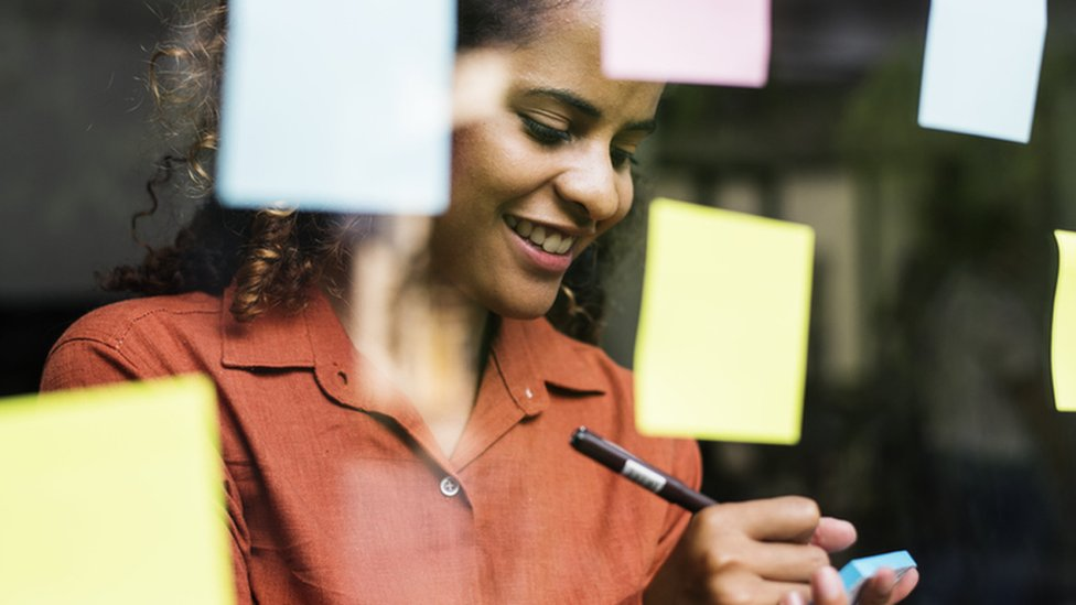 A woman writes on a post it note