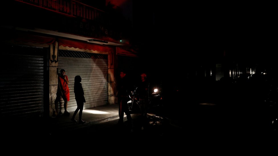 People use the light of a motorcycle to illuminate them as they talk on the street during a blackout in Caracas