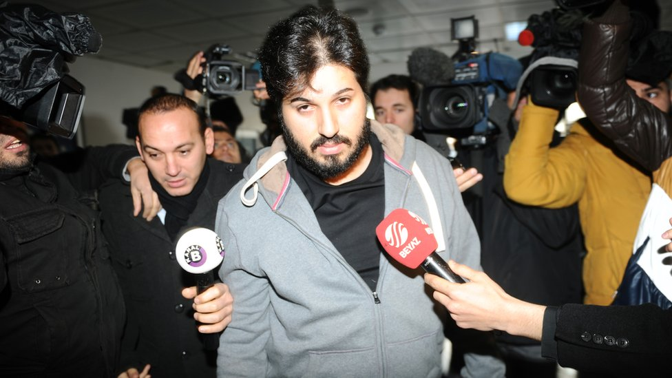 Detained Azerbaijani businessman Reza Zarrab is surrounded by journalists as he arrives at a police centre in Istanbul on 17 December 2013