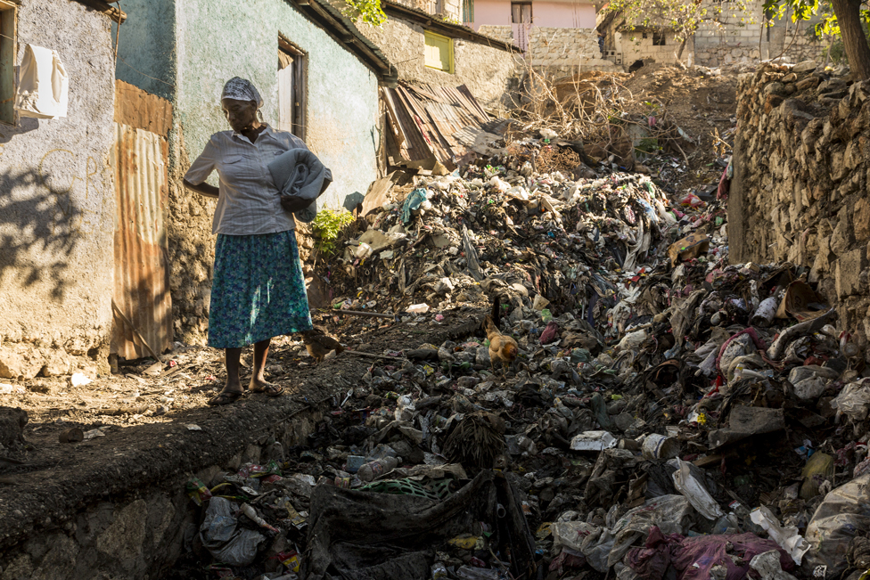 A woman stands in front of rubbish washed down the mountain